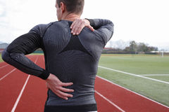 Athletic fitness man with neck and back pain. Sports exercising injury. Stock Photo
