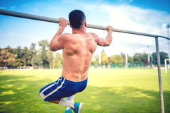Athletic fitness trainer, basketball and football player training out on the field. Chin-ups and Chin-ups training day Royalty Free Stock Photography