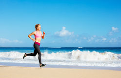 Athletic Fitness Woman Running on the Beach Stock Images
