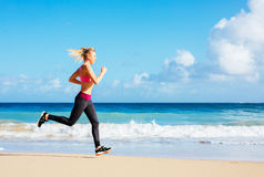 Athletic Fitness Woman Running on the Beach Royalty Free Stock Image