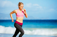 Athletic Fitness Woman Running on the Beach Royalty Free Stock Photography