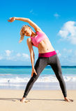 Athletic Fitness Woman Stretching At the Beach, Royalty Free Stock Photos