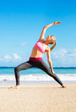 Athletic Fitness Woman Stretching At the Beach, Stock Photography