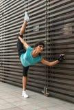 Athletic flexible young woman doing yoga standing split exercise Stock Photo