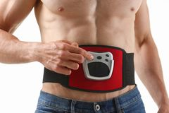 Athletic folded man uses an electric belt simulator for training a press. White stock image