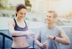 Athletic girl and active man standing near stadium before training Royalty Free Stock Photo