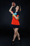 Athletic girl with a ball in colorful dress in studio on dark ba Royalty Free Stock Photography