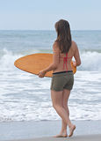Athletic girl on the beach. Athletic teen girl prepares for a wave to bring her the surf that she needs to skim on the water surface.  Room for text at the top Stock Images