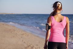 Athletic girl on the beach from the back. Sports girl in headphones on the beach in front of a run Stock Images