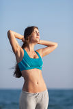 Athletic girl on beach. Young long-haired woman standing against of sea with hands on head. She sunbathes with eyes closed Royalty Free Stock Photography