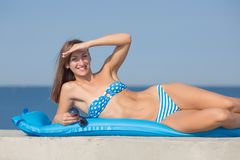 Athletic girl in blue bikini resting at the sea. Slim girl in swimwear lying on blue inflatable pool raft leaning on elbow, she looking at camera smiling royalty free stock images