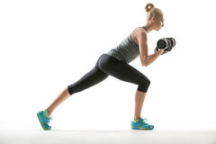 Athletic girl does exercise with dumbbells Royalty Free Stock Photos
