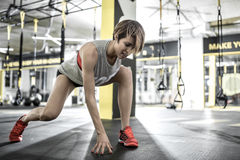 Athletic girl does stretching in gym. Cute smiling girl with does stretching in the gym on the background of the hanging TRX straps. She wears a red top and Stock Images