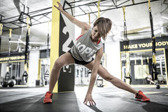 Athletic girl does stretching in gym. Sportive girl with parted lips does stretching in the gym on the background of the hanging TRX straps. She wears a red top Royalty Free Stock Images