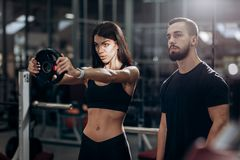 Athletic girl doing exercise for the muscles of the arms with weight in the gym under the supervision of a coach stock photo