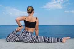 Athletic girl doing exercises against the sea, rear view Stock Images