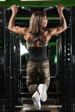Athletic girl doing pull up exercise on horizontal bar. Fitness woman workout in gym.  royalty free stock photos