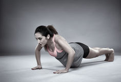 Athletic girl doing pushups Stock Images