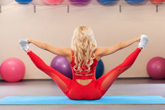 Athletic girl doing stretching exercise in the fitness room. Sport woman sits on a twine Royalty Free Stock Photo
