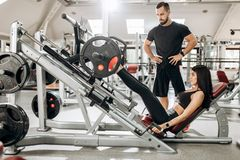 Athletic girl dressed in black sport clothes is lifting weights with her legs in the gym under the supervision of a stock photography