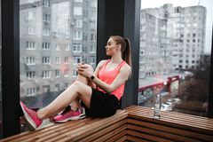 The athletic girl dressed sport shorts and t-shirt is sitting on the wooden windowsill in the modern gym royalty free stock image