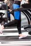 The athletic girl dressed in a sportswear is running on the treadmill in front of the windows in the modern gym royalty free stock image