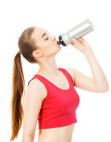 Athletic girl drinks water after exercising isolated in white ba. Athletic girl drinks water after exercising Royalty Free Stock Photos