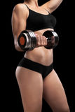 Athletic girl with dumbbells in hand. Royalty Free Stock Images