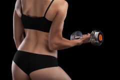 Athletic girl with dumbbells in hand. Stock Photos