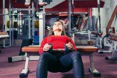 Athletic girl engaged in fitness. woman doing exercise with dumbbell on the bench royalty free stock photos