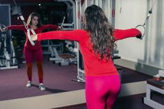 Athletic girl engaged in the gym on the simulator. sports fitness and weightlifting. woman looks into of the mirror royalty free stock photography