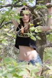 Athletic girl with flat belly hanging from branch of tree Stock Photo