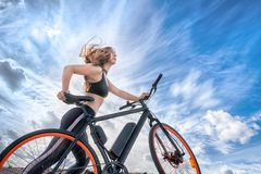 Athletic girl with hair flying in the wind leading electric bike. Outdoor portrait against blue cloudy sky royalty free stock photo