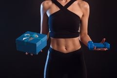 Athletic girl holding dumbbells and gift box in her hands royalty free stock photo