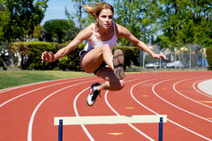 Athletic girl hurdling. At the track Stock Photos