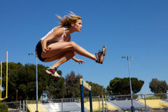 Athletic girl hurdling Royalty Free Stock Photos