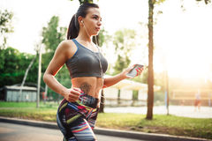Athletic girl jogging with headphones in park Royalty Free Stock Image