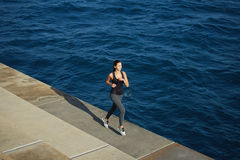 Athletic girl jogging over amazing big waves background at sunny day Stock Image