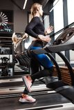 The athletic girl with long blond hair dressed in a sportswear is running on the treadmill in front of the windows in royalty free stock photography