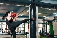 Athletic girl makes a kick on the punching bag. woman in boxing gloves trains martial arts. royalty free stock photo