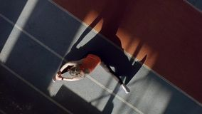 Sportive blonde woman training at indoor stadium. Athletic girl in an orange T-shirt with black pants and light sneakers is doing a stretching exercises at the stock video footage