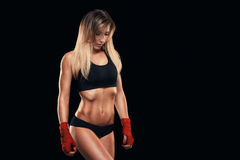 Athletic girl posing in red bandages, isolated on the dark background boxing fighter kickbox Stock Photo
