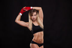Athletic girl posing in red bandages, isolated on the dark background boxing fighter kickbox Royalty Free Stock Images