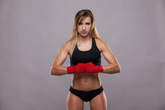 Athletic girl posing in red bandages, isolated on the grey background boxing fighter kickbox Royalty Free Stock Photography