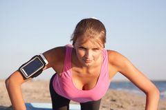 Athletic girl push-ups on the beach. Athletic girl push-ups  the beach on sunny day Stock Photography