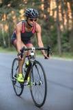 Athletic girl rides a bike. Delightful sportive girl rides a bike on the road on the nature background. She wears black-pink sportswear, a stopwatch, a black Royalty Free Stock Image