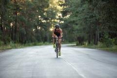 Athletic girl rides a bike Stock Photos