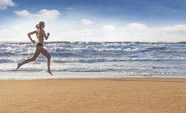 Athletic girl running along beach Royalty Free Stock Photography