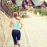 Athletic girl running on street in mountains town Royalty Free Stock Image