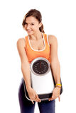 Athletic girl with a scale. Portrait of a beautiful athletic girl holding a scale, isolated on white Royalty Free Stock Photo
